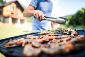Blog - Unrecognizable man cooking seafood on a barbecue grill in the backyard.